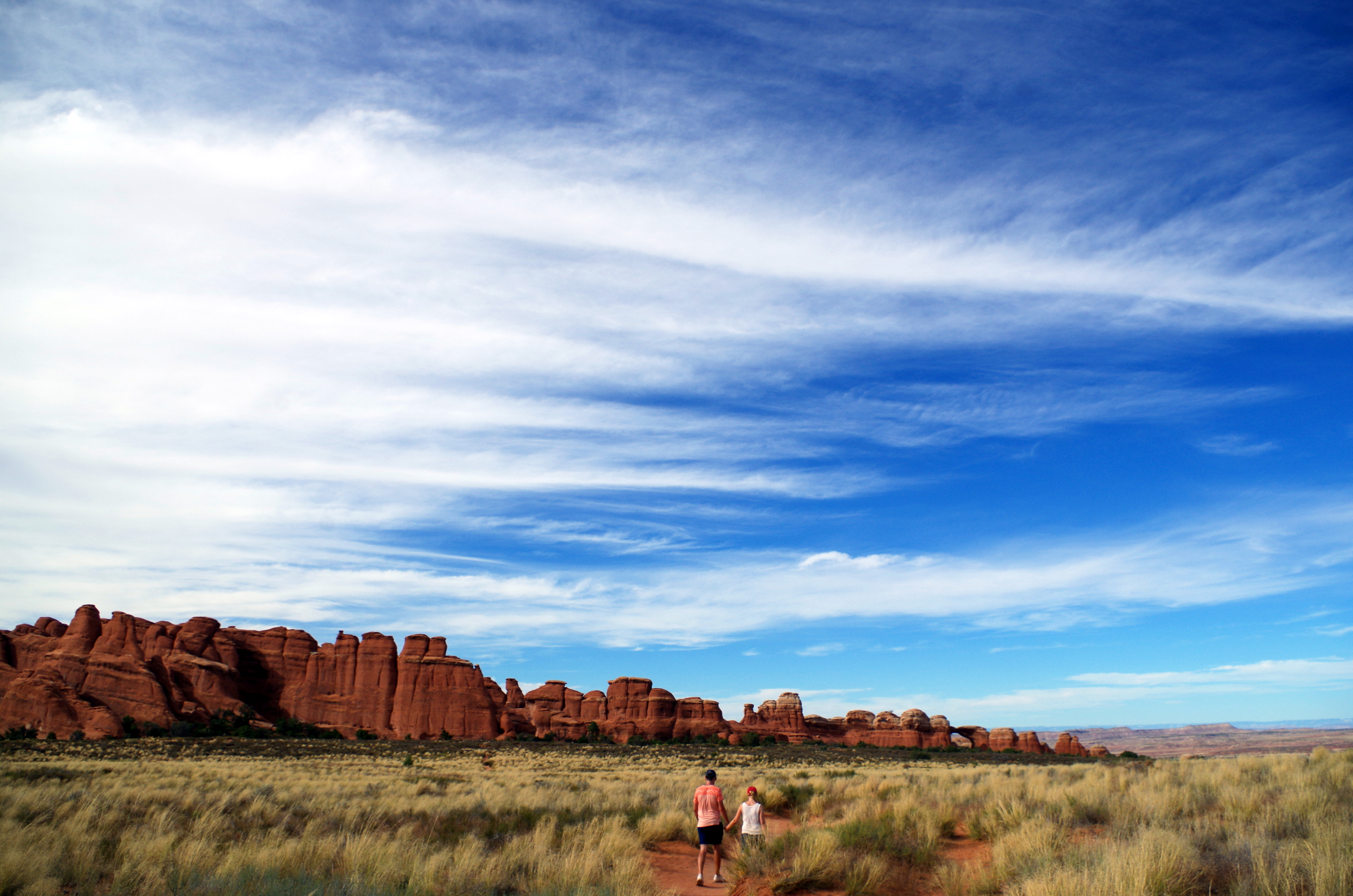 Zwischen den Felsformationen findet ihr im Arches NP auch weite Wege, die Euch durch Graslandschaften vorbei an Sträuchern und wilden Tieren führen.